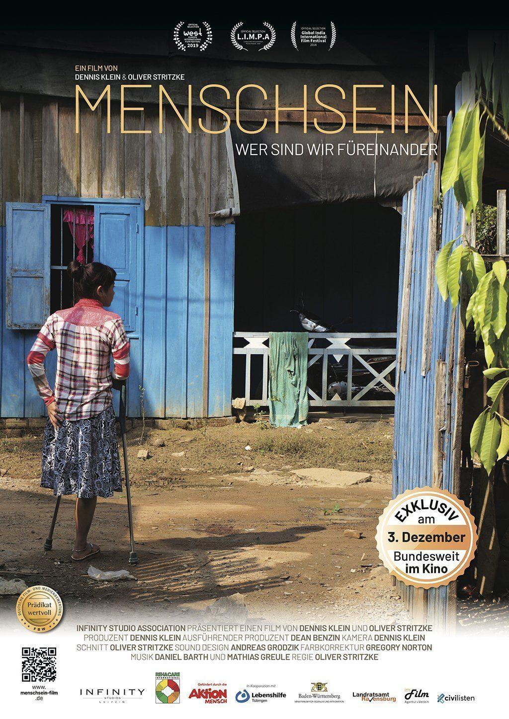 Frau mit einem Bein und Gehilfe steht vor einer blauen Hütte